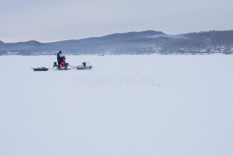 O carro de neve com pescadores está montando ao longo do lago do inverno fotografia de stock