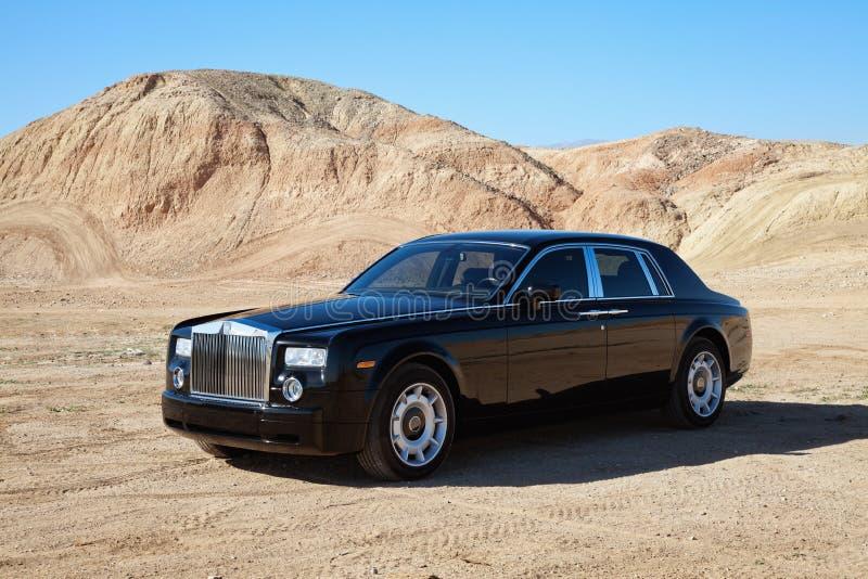 O carro de Rolls Royce estacionou na estrada unpaved na frente das montanhas imagem de stock royalty free