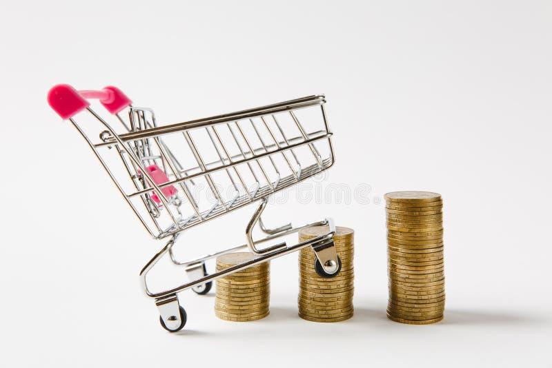 O carro do impulso do mantimento do supermercado para comprar com o punho plástico cor-de-rosa corre sobre pilhas de moedas doura fotos de stock
