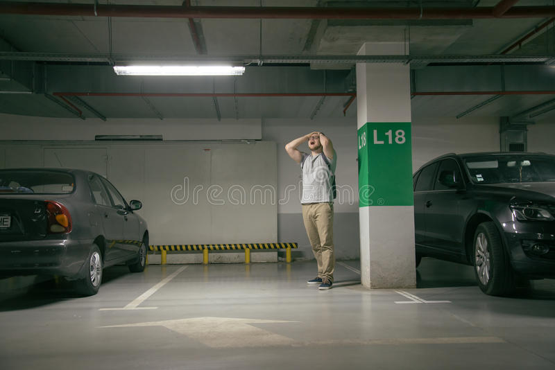 O carro do ` s do homem foi roubado, pode carro do achado do ` t no estacionamento subterrâneo imagem de stock royalty free