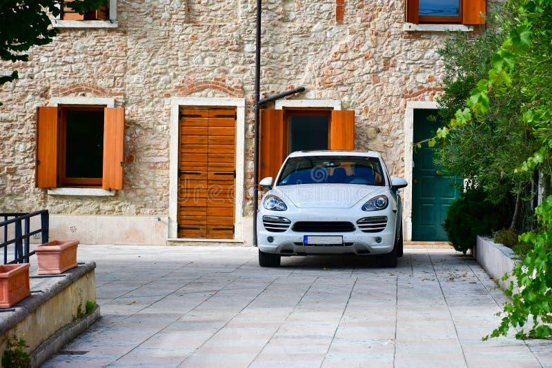 o carro estacionou na frente da casa de pedra em San Zeno di Montagna, Itália fotografia de stock royalty free