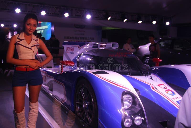 O carro F1 e os modelos na exposição do automóvel foto de stock
