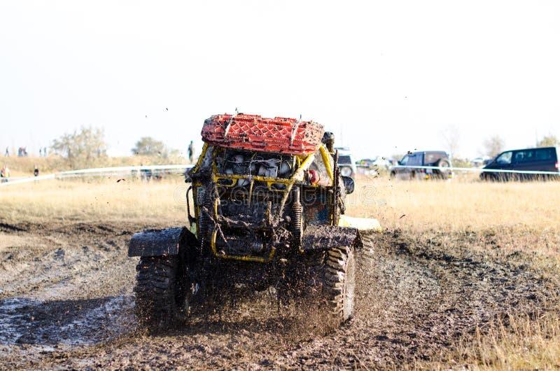 O carro fora de estrada em uma poça que faz a lama espirra foto de stock