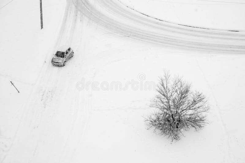 O carro gerencie na volta nevado da estrada no inverno durante a queda de neve imagem de stock royalty free