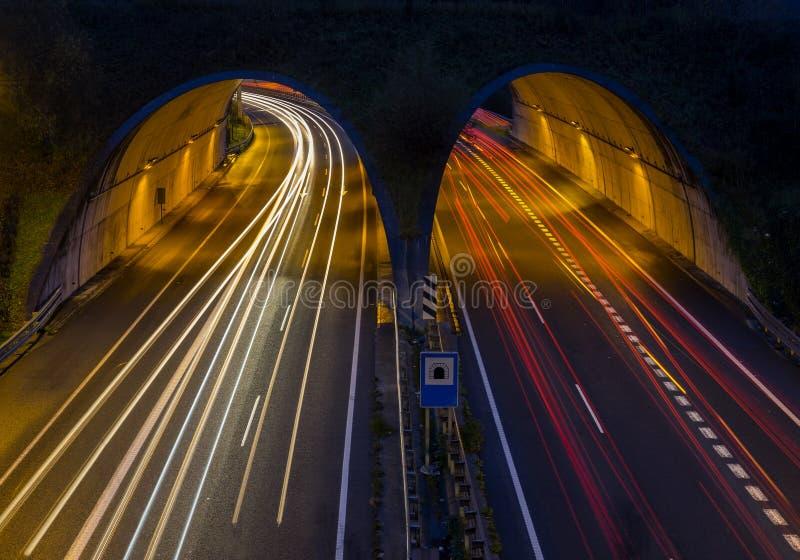 O carro ilumina atravessar um túnel em Hernani imagem de stock