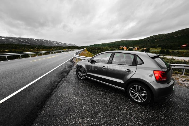 O carro moderno cinzento está estacionando ao lado de uma estrada pavimentada rural que conduza através da natureza de Noruega ta foto de stock