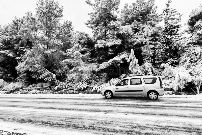 O carro na estrada asfaltada do inverno cobriu a neve fotografia de stock