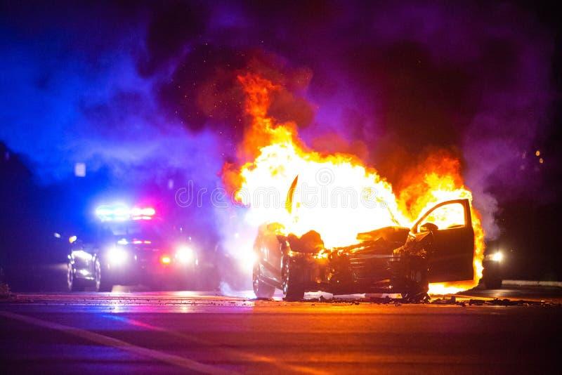 O carro no fogo na noite com polícia ilumina-se no fundo fotos de stock