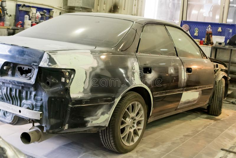 O carro preto no corpo do sedan é preparado pintando foto de stock royalty free