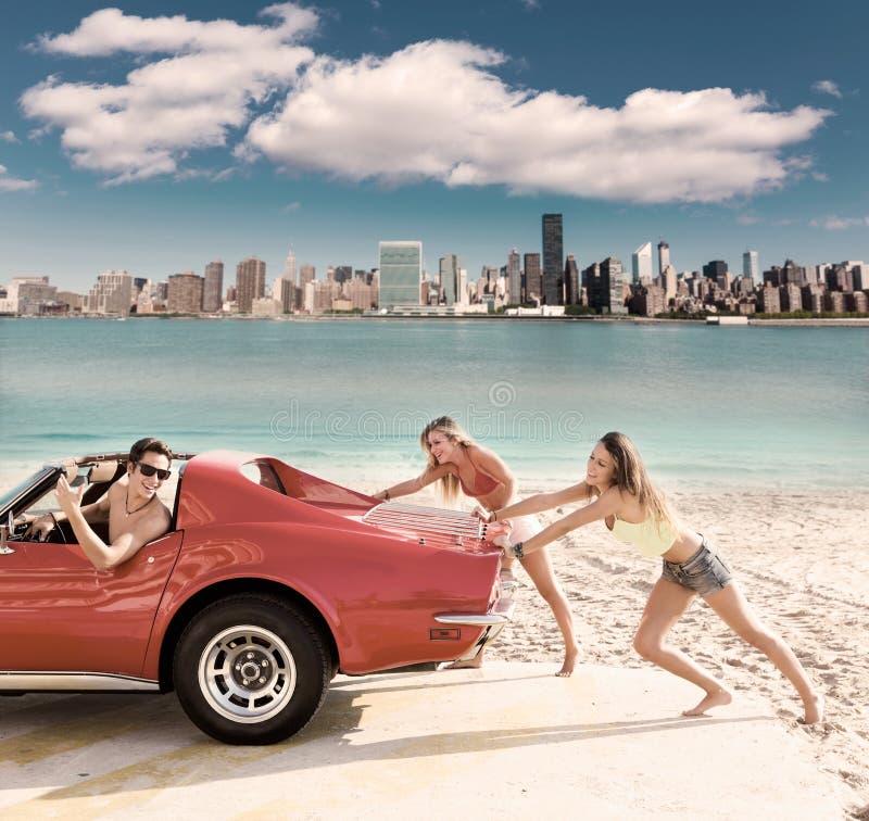 O carro que empurra meninas adolescentes humor a condução engraçada do indivíduo fotografia de stock