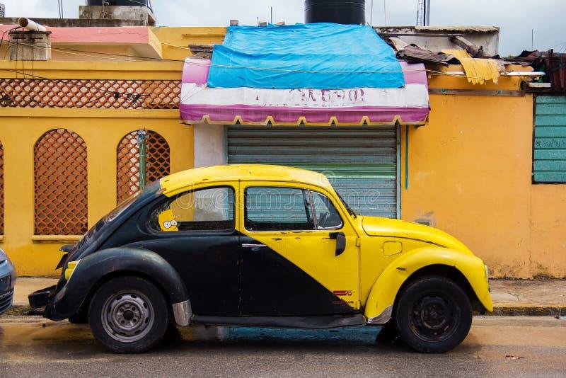 O carro retro amarelo e preto Volkswagen Beetle estacionou na rua velha imagem de stock