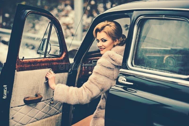 o Carro retro e repara??o de autom?veis da cole??o pelo motorista Mulher 'sexy' no casaco de pele escolta imagem de stock royalty free