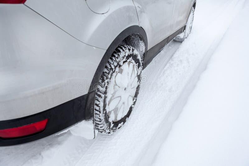 O carro roda dentro o pneumático do inverno que conduz na neve, fim acima foto de stock