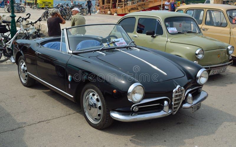 O carro superior aberto preto clássico dos esportes de Alfa Romeo estacionou no stree imagens de stock royalty free