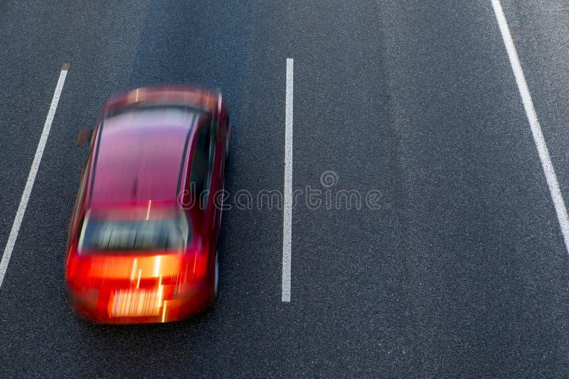 O carro vermelho corre rapidamente na estrada pela pista esquerda no por do sol Espaço da vista superior e da cópia no lado direi imagem de stock royalty free