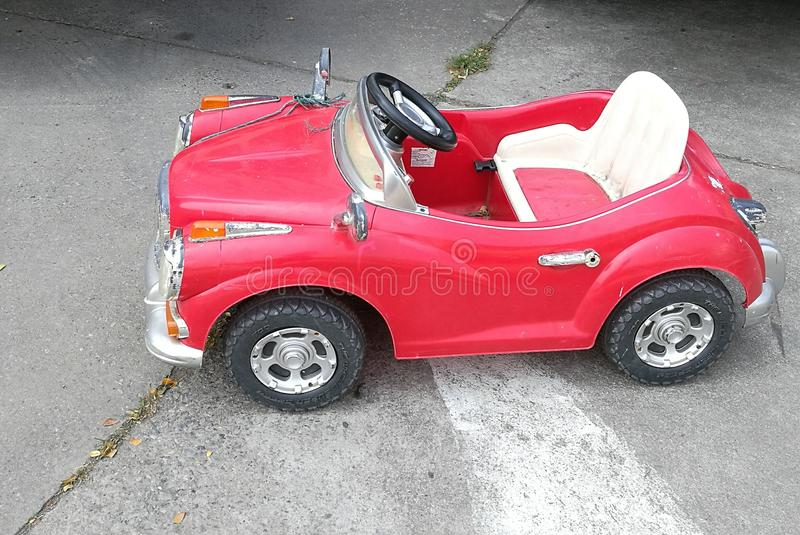 O carro vermelho do brinquedo do vintage para crianças e criança na rua, carro do brinquedo estacionou na estrada fotos de stock