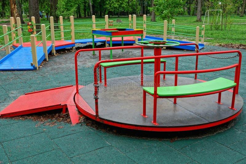 O carrossel colorido redondo do metal das crianças está no campo de jogos fotografia de stock royalty free