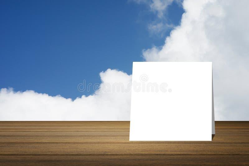 O cartão branco pôs sobre a mesa de madeira ou o assoalho de madeira sobre o fundo do céu azul e da nuvem uso para o presente ou  foto de stock royalty free