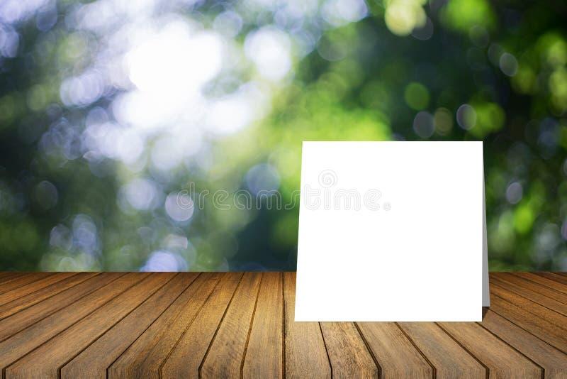 O cartão branco pôs sobre a mesa de madeira ou o assoalho de madeira sobre o fundo verde borrado da natureza da árvore uso para o imagem de stock