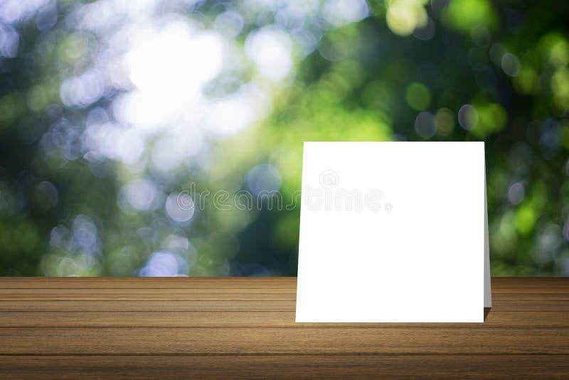 O cartão branco pôs sobre a mesa de madeira ou o assoalho de madeira sobre o fundo verde borrado da natureza da árvore uso para o fotografia de stock royalty free