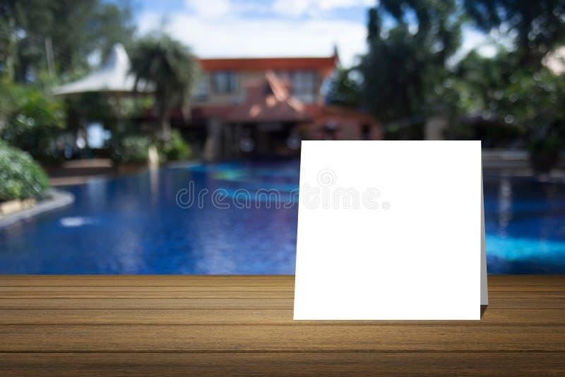 O cartão branco pôs sobre a mesa de madeira ou o assoalho de madeira sobre a piscina borrada no fundo do recurso uso para o prese imagens de stock royalty free