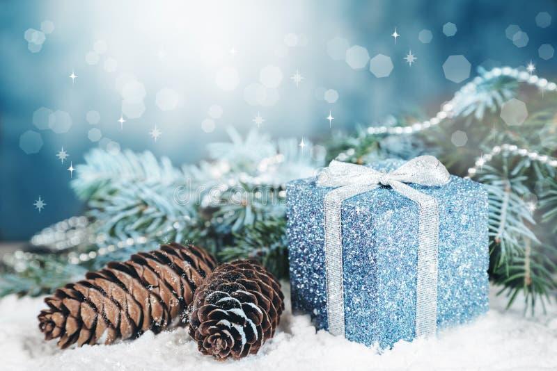 O cartão de Natal, cones do presente, abeto ramifica, decorações com bokeh imagens de stock royalty free