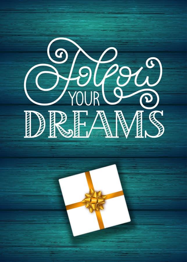 O cartão de presente de época natalícia com rotulação da mão segue seus sonhos e presente no fundo de madeira ilustração stock