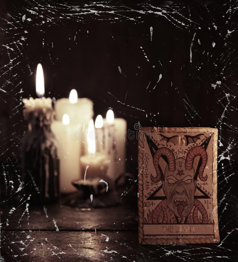 O cartão de tarô com o diabo contra fundo defocused das velas foto de stock