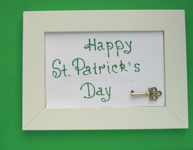 O cartão do dia de St Patrick com quadro branco no fundo verde, fecha à riqueza e aos tesouros foto de stock