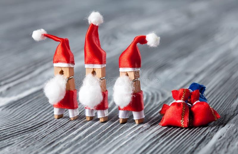 O cartão do Xmas com o pregador de roupa engraçado Santa do brinquedo do grupo, presente vermelho ensaca no fundo de madeira boni imagens de stock
