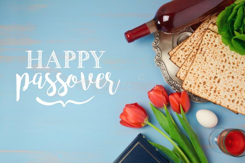 O cartão judaico de Pesah da páscoa judaica do feriado com placa, matzoh e tulipa do seder floresce no fundo rústico de madeira foto de stock