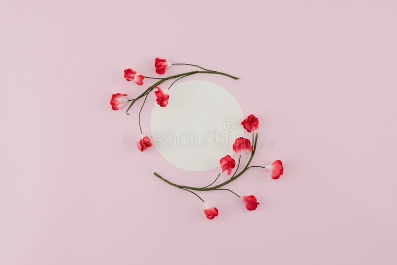 O cartão redondo branco decora com as flores de papel vermelhas imagens de stock royalty free