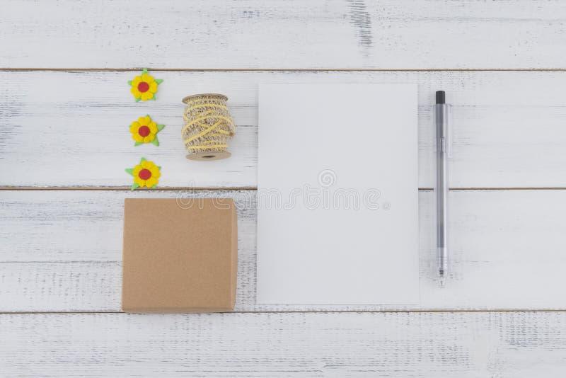 O cartão vazio branco, a caixa de presente marrom e a pena decoram com as flores de papel amarelas e corda marrom foto de stock