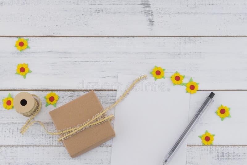 O cartão vazio branco, a caixa de presente marrom e a pena decoram com as flores de papel amarelas e corda marrom fotos de stock royalty free