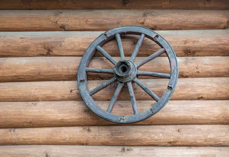 O cartwheel velho pendura na parede de uma casa de log imagens de stock royalty free