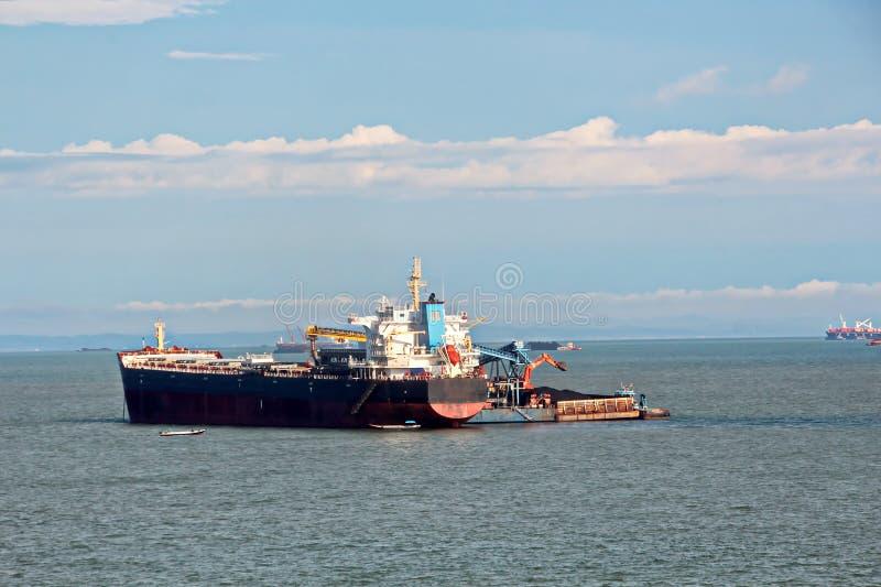 O carvão da carga das barcas da carga em um portador de maioria que usa o navio cranes e garras no porto de Samarinda, Indonésia imagens de stock