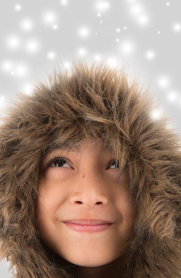 O casaco de pele vestindo do rapaz pequeno protege das despesas gerais frias da neve imagens de stock