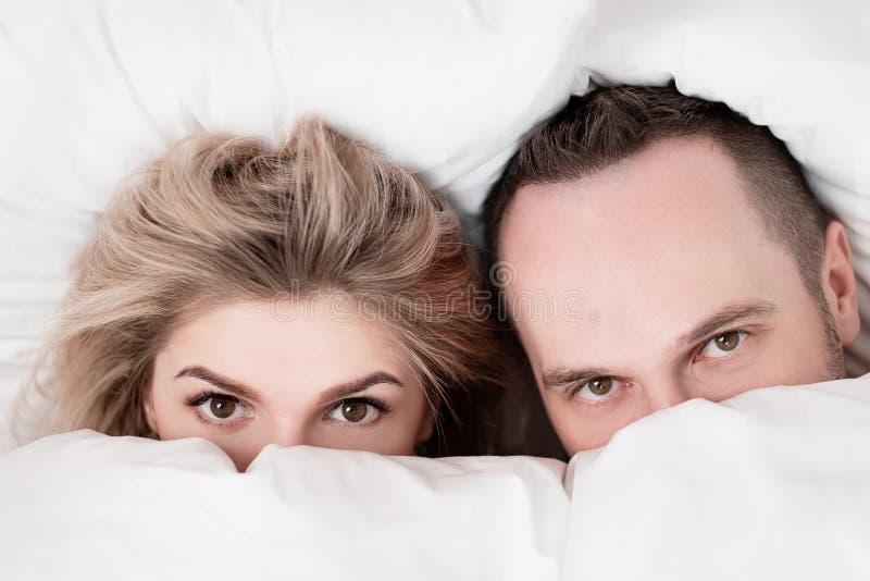 O casal, o homem e a mulher, estão encontrando-se na cama, estão abraçando-se e estão dormindo-se no fundamento branco Escondendo foto de stock