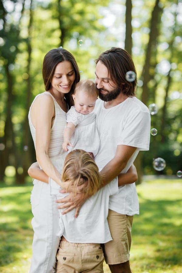 O casal vestido na roupa branca é de sorriso e guardando pouca filha nos braços ao abraçar o filho imagem de stock royalty free
