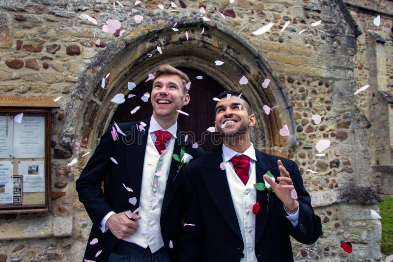 O casamento alegre, noivos sae da igreja da vila após o casamento aos sorrisos e aos confetes imagens de stock royalty free