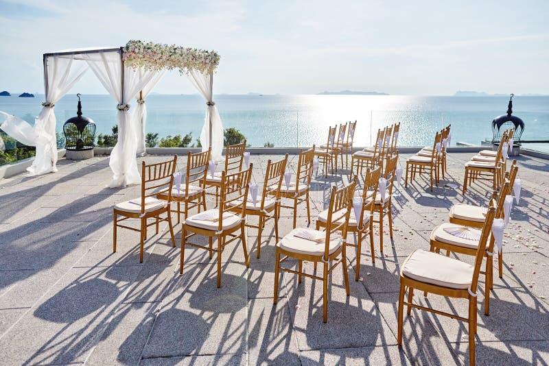 O casamento arqueia, flores, decoração floral, oceano com fundo da reflexão fotografia de stock