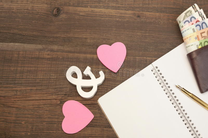 O casamento custa o conceito Corações, pena, papel, dinheiro em Backgro de madeira fotografia de stock royalty free