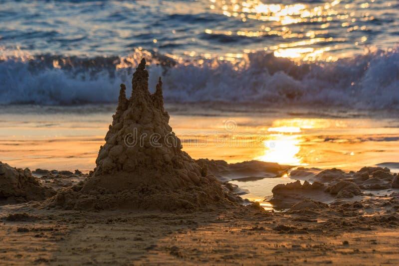 O castelo da areia está no por do sol A trilha solar está na areia Fundo foto de stock
