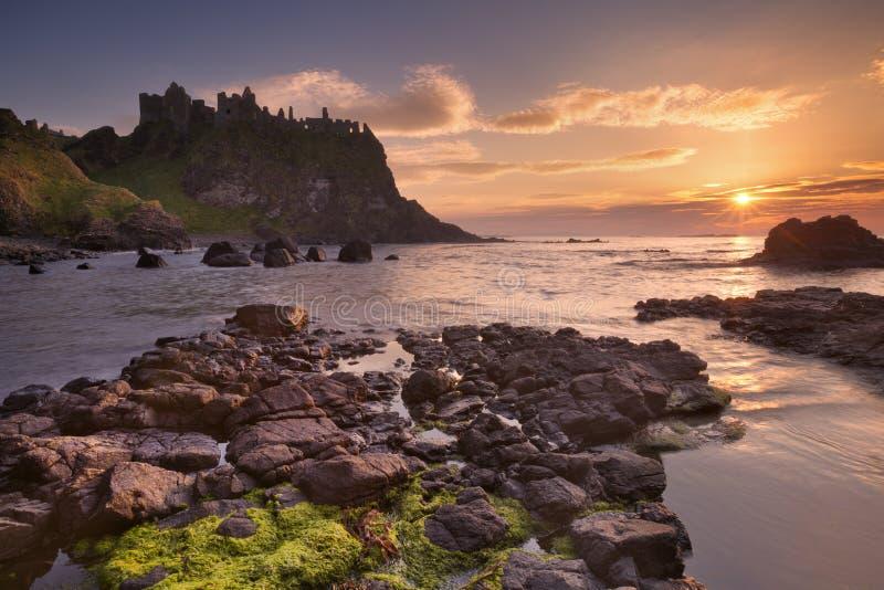 O Castelo de Dunluce na Irlanda do Norte ao pôr do sol imagem de stock