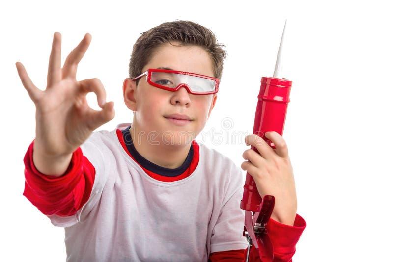 O Caucasian liso-descascou óculos de proteção vermelhos boywearing e guardar um Ca fotografia de stock royalty free