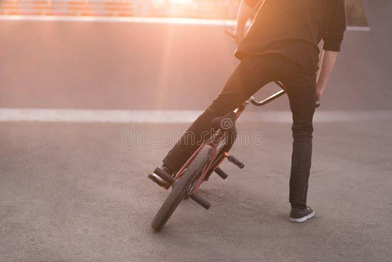 O cavaleiro de Bmx executa truques em uma bicicleta do bmx em um parque do patim no fundo do por do sol Conceito de BMX Copyspace fotografia de stock