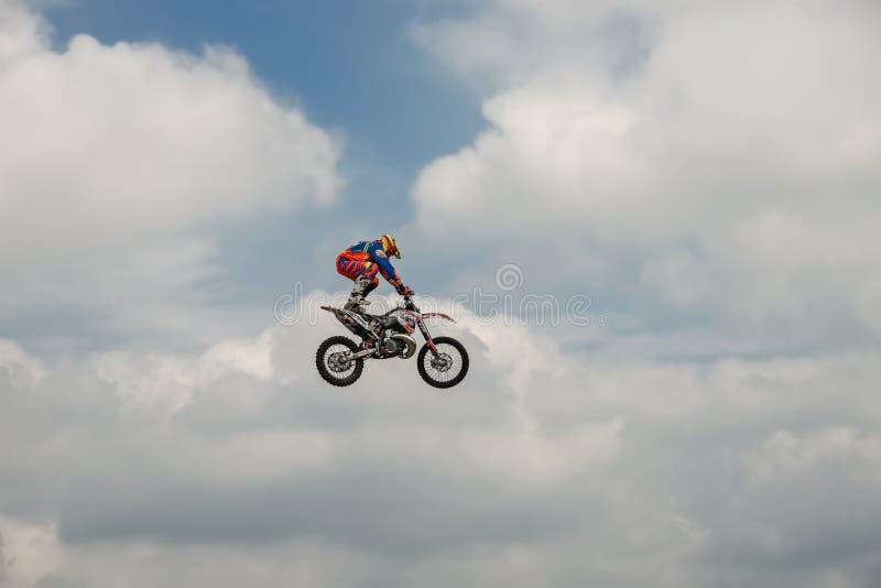 O cavaleiro do motocross do estilo livre realiza um truque com a motocicleta no fundo do céu azul da nuvem Esporte extremo Alemão imagem de stock royalty free
