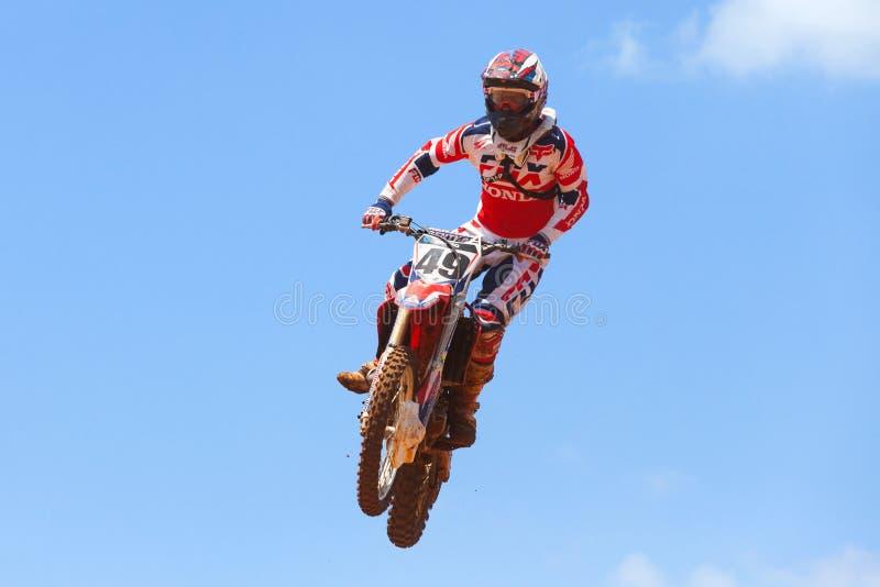 O cavaleiro e a bicicleta do motocross que cancelam um tabletop saltam foto de stock royalty free