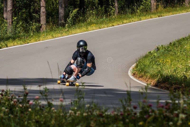 O cavaleiro em declive de Longboard faz rapidamente em uma volta fotografia de stock royalty free