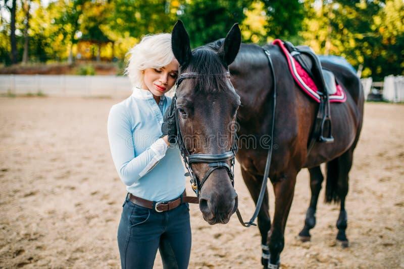 O cavaleiro fêmea abraça seu cavalo, equitação imagens de stock